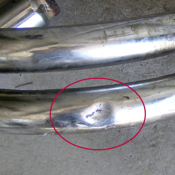 Small dent on header pipe #1